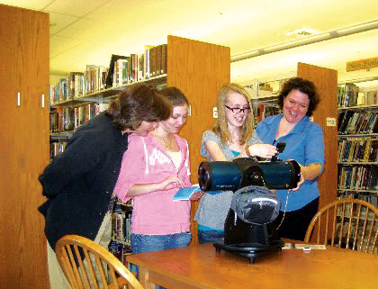 Conway Public Library patrons Janis, Maria, and Jenn take a closer look at the library's new Orion StarBlast 4.5 with Library Director Tara.